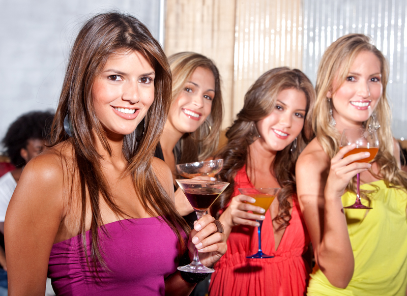 group of happy girls smiling at a party with some cocktail drinks